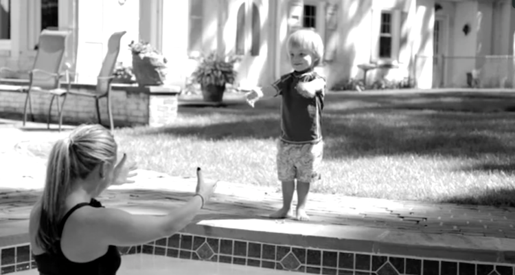 Small boy at the edge of a swimming pool reaches out to mother
