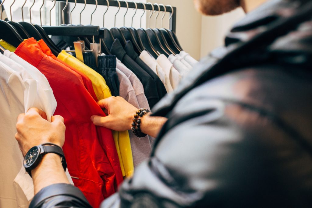 Close up of man's hands browsing clothes on clothes rack