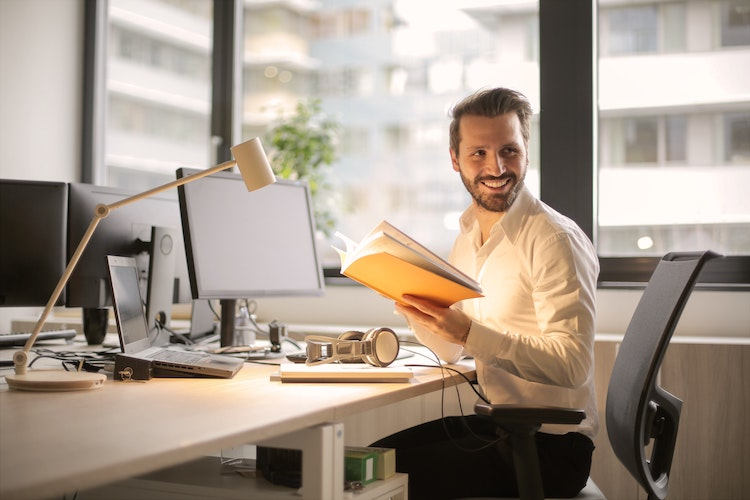 A smiling business man sits in front of a computer on his desk holding a file