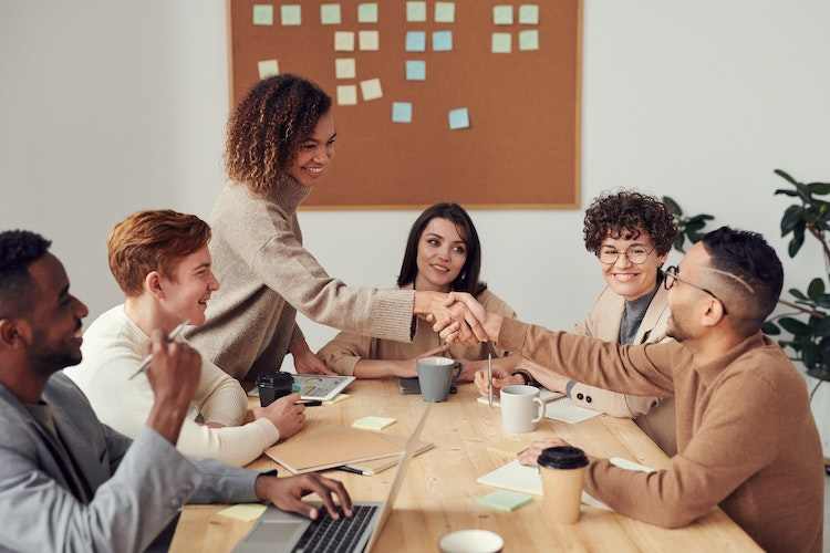 Young co-workers gather round a work table
