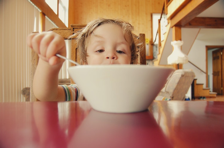 Blonde haired child enjoys breakfast from white cereal bowl