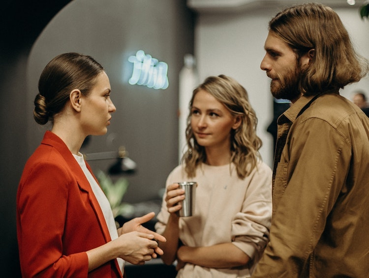 Two women and one man in the workspace deep in conversation