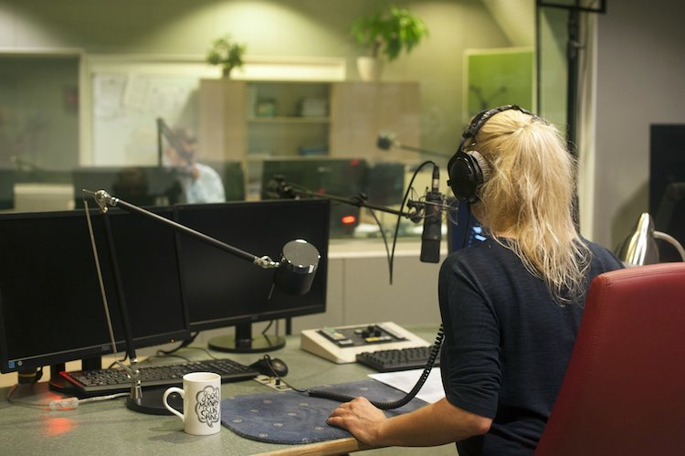 Blonde woman at radio station talks into microphone