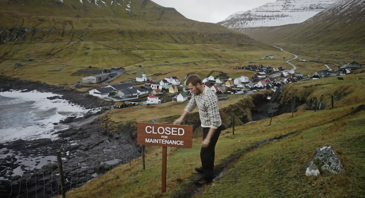 Man puts up a board on Faroe Islands as part of Closed for Business travel PR campaign