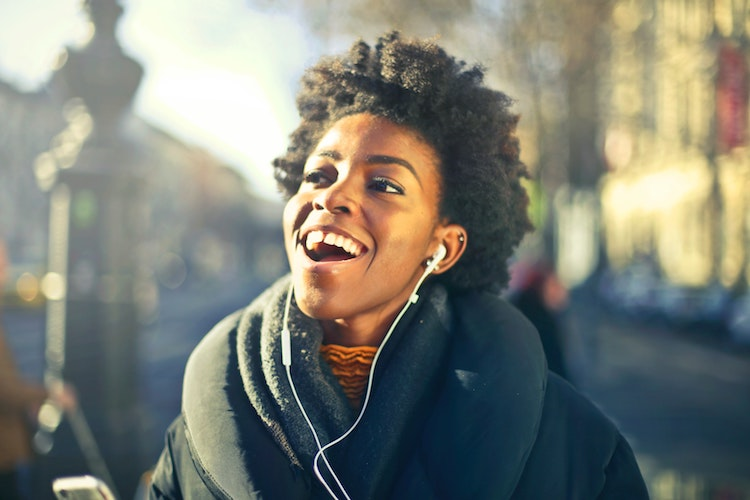Woman laughs as she listens to podcast
