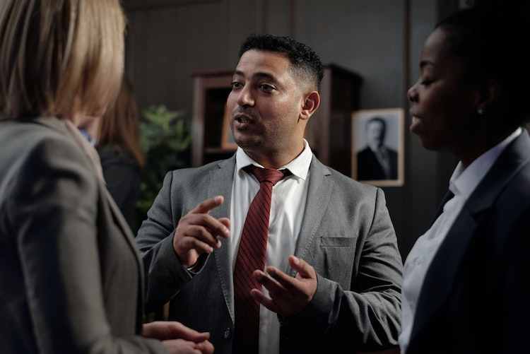 A business man holds a meeting standing up and speaks to two work colleagues