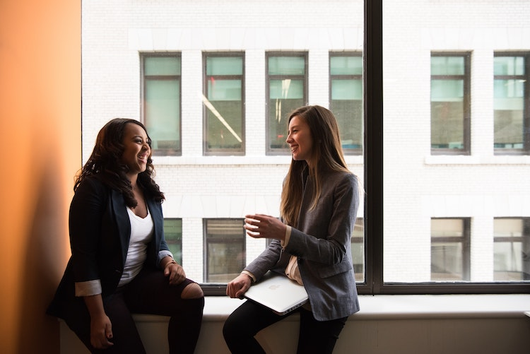 Two business women speak face to face