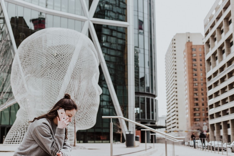 Woman talks on mobile phone while sitting in front of a wire head installation in city centre