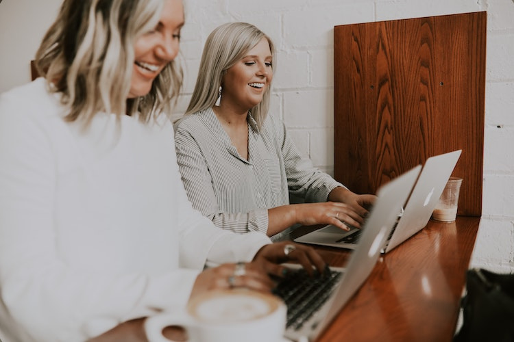 Blonde women sit in front of their laptops smiling