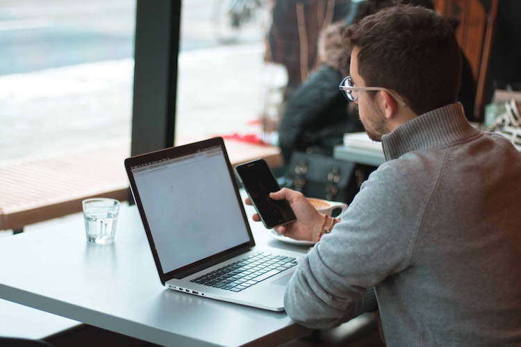 Guy looks at laptop in front of window