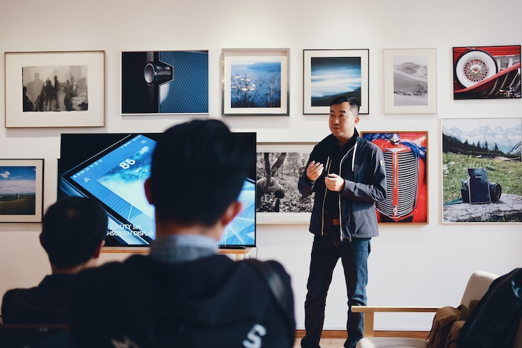 Man giving talk in front of screen