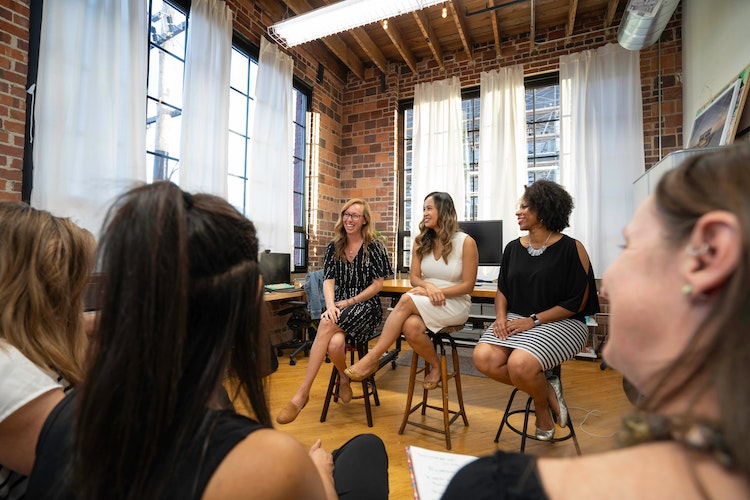 Women sit on stools and face small audience for presentation