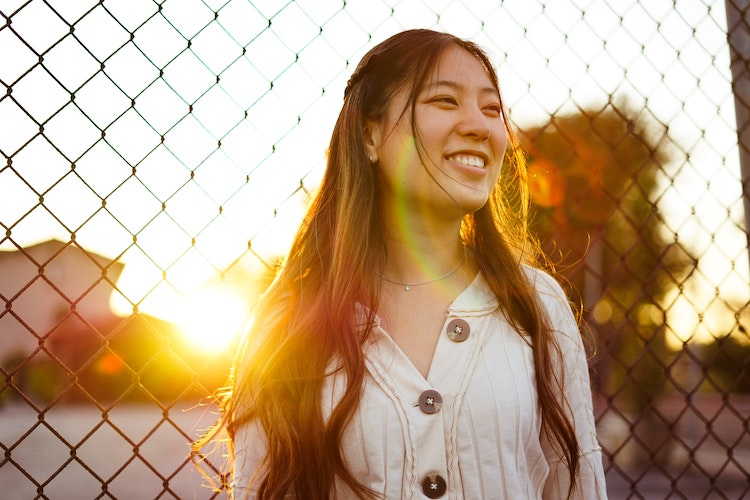 Young Asian woman smiles in sunshine