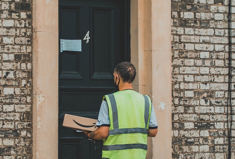 Amazon delivery driver with parcel at closed front door
